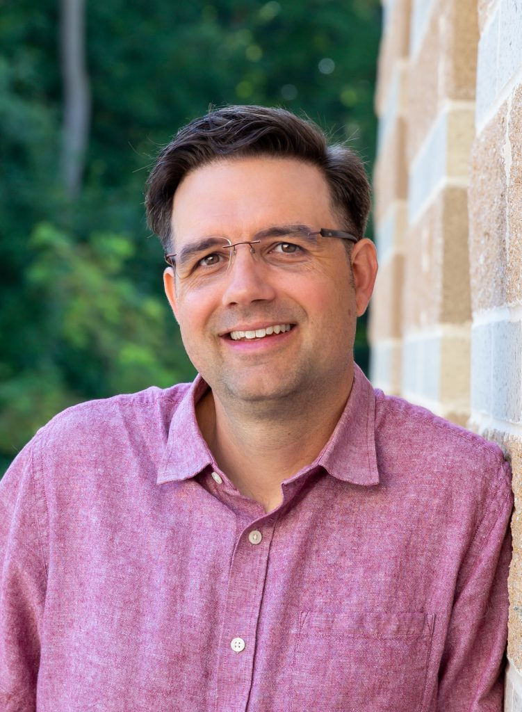Dr. Matt Fitzpatrick leaning against red brick exterior with trees in background.